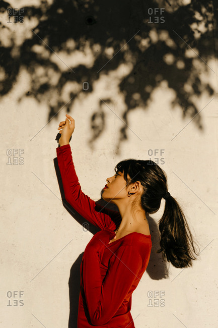 Beautiful woman with hand raised standing by tree shadow on wall