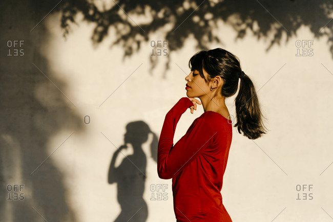 Young woman standing with hand on chin by tree shadow during sunset