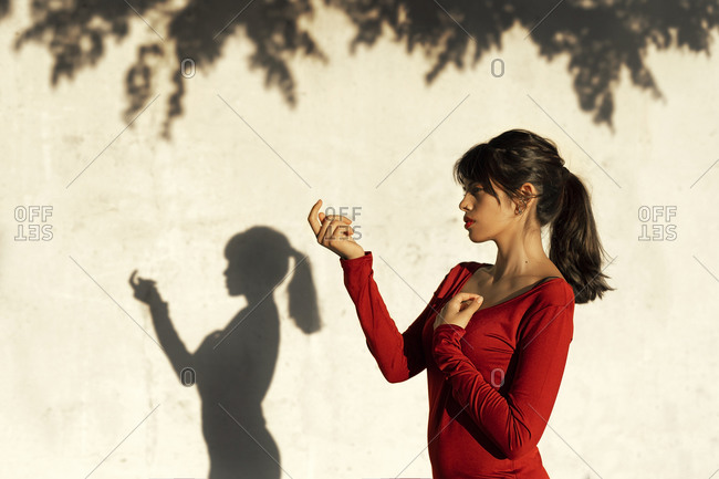 Contemplating woman doing hand gesture while standing by tree shadow