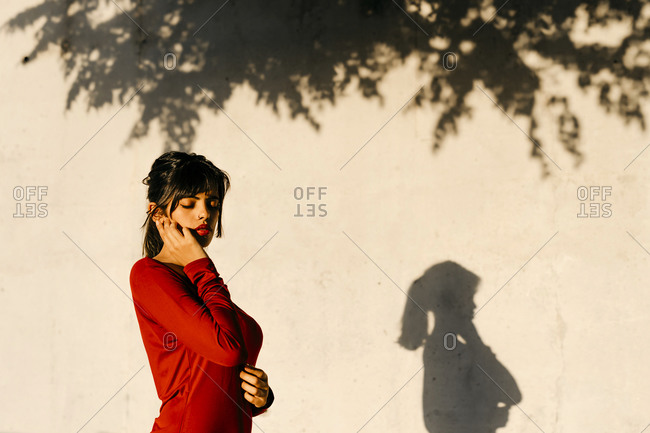 Thoughtful woman standing with eyes closed by shadow on wall during sunset