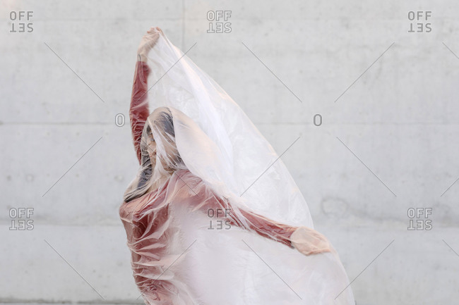 Young woman doing hand gesture while wrapped inside plastic