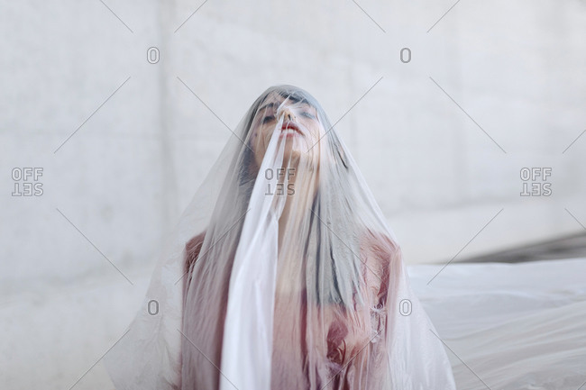 Woman covered with plastic around her body and face