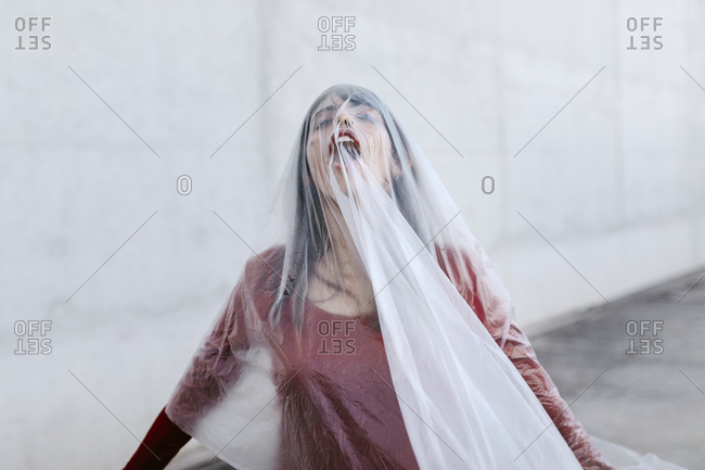 Young woman with mouth open covered under plastic