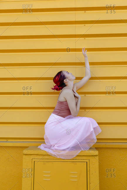 Young woman ballet dancing on seat against yellow wall