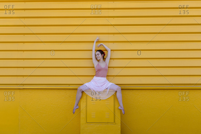 Smiling ballerina with arms raised dancing on seat against yellow wall