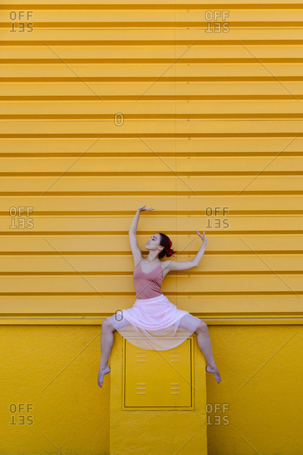 Young woman with arms raised dancing on seat against yellow wall
