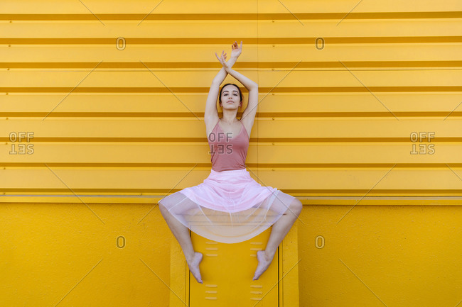 Confident young woman with arms raised ballet dancing on seat against yellow wall