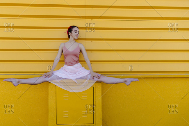 Ballerina doing the splits on seat against yellow wall