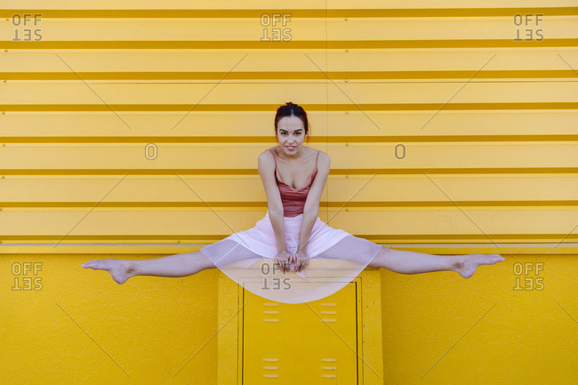 Young woman doing splits while ballet dancing on seat against yellow wall