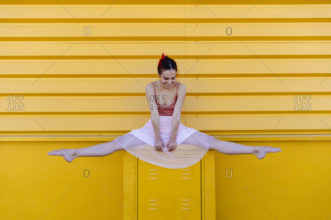 Ballet dancer doing splits on seat against yellow wall