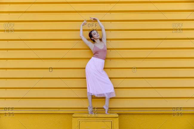 Ballerina with arms raised posing while standing on seat against yellow wall