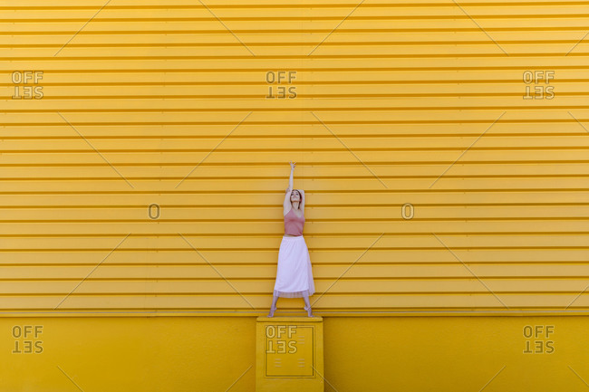 Ballerina with tiptoe dancing on seat against yellow wall