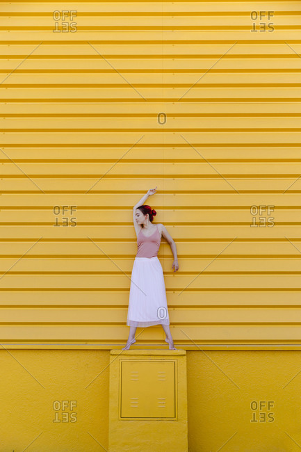 Ballerina with arms raised dancing on seat against yellow wall