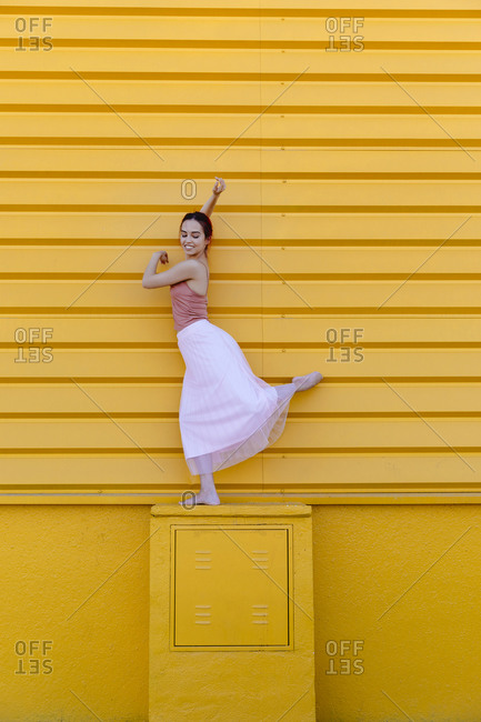 Smiling ballet dancer dancing on seat by yellow wall