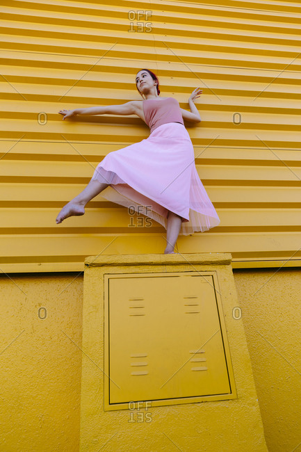 Ballet dancer dancing gracefully on seat against yellow wall