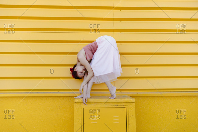 Ballerina bending while dancing on seat against yellow wall
