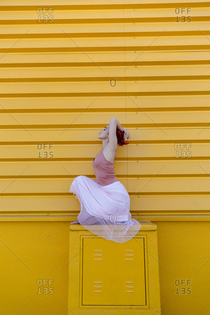 Ballerina with arms raised crouching while dancing on seat against yellow wall