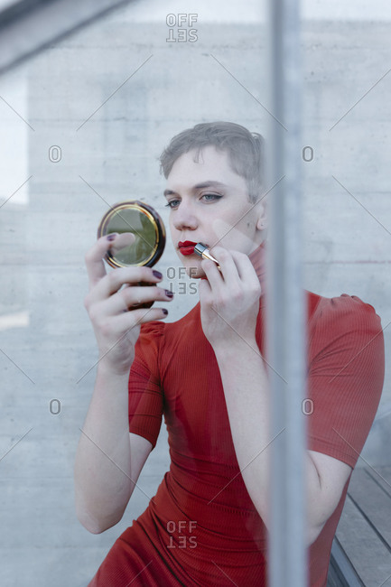 Trans young man applying lipstick while sitting on steps seen through glass