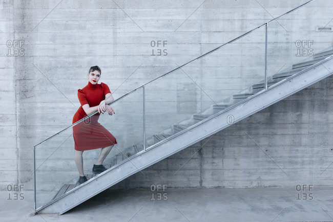 Trans young man wearing red dress standing on steps by railing