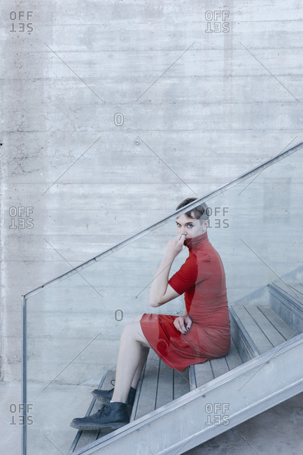 Trans young man wearing red dress sitting on steps seen through glass railing