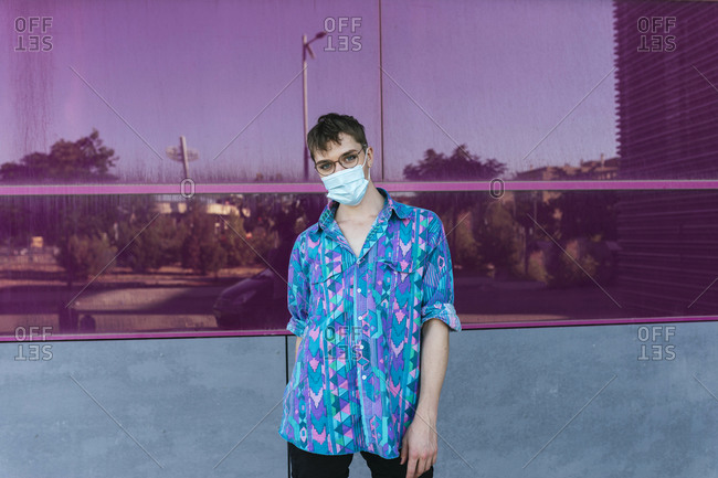 Non-binary person wearing face mask while standing against pink glass wall