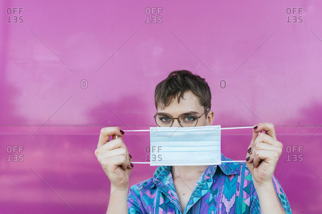 Non-binary person holding protective face mask while standing against pink wall