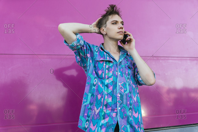 Non-binary person talking on mobile phone while standing against pink wall