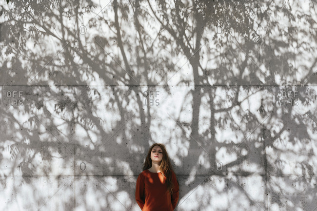 Young woman with hands behind back standing against tree shadow wall