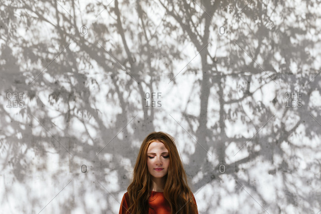Redhead woman standing with eyes closed against tree shadow wall