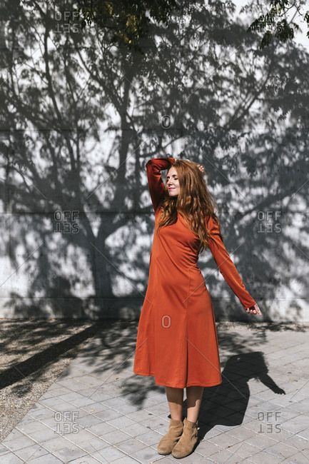 Young woman with hand in hair standing against tree shadow wall