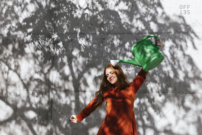 Woman holding watering can up while standing against tree shadow wall