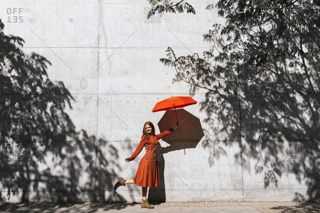 Smiling woman holding red umbrella while standing against tree shadow wall