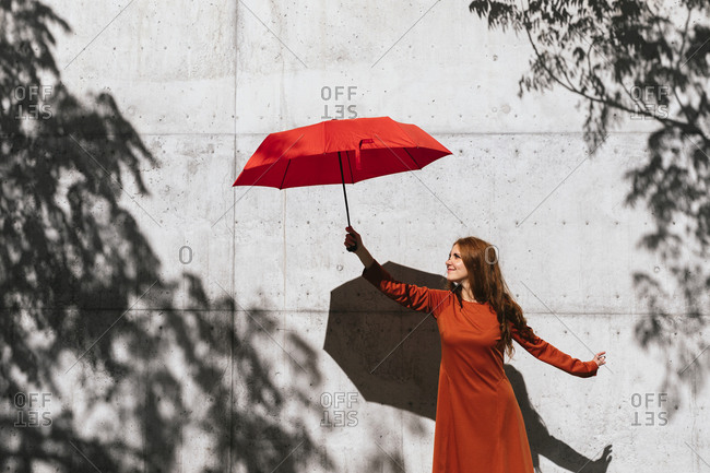 Smiling redhead woman holding umbrella while standing against tree shadow wall
