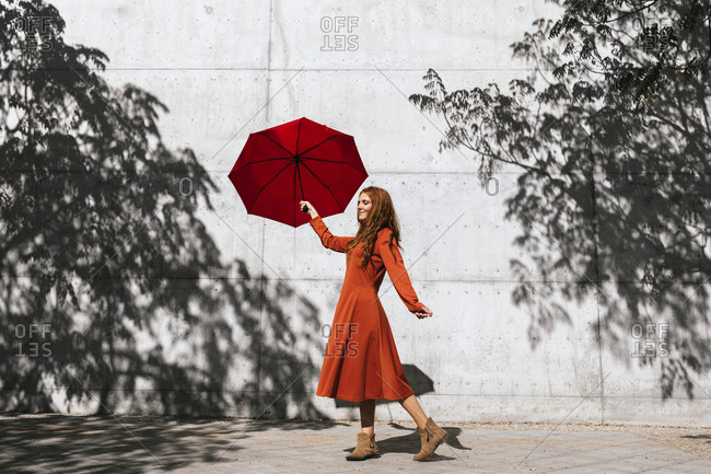 Woman in red dress holding red umbrella while standing against tree shadow wall
