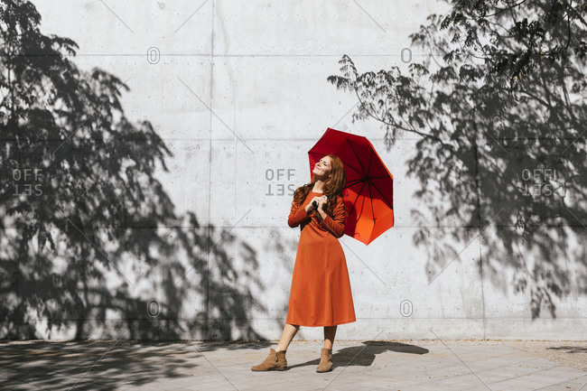 Smiling woman holding umbrella while standing against tree shadow wall