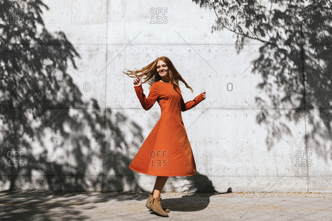 Happy woman dancing against tree shadow wall