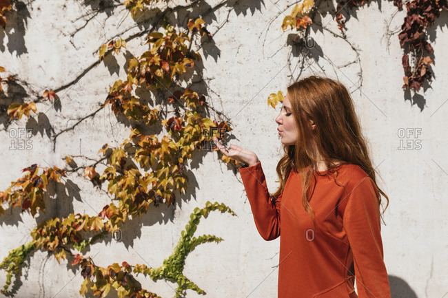 Young woman blowing kiss while standing against ivy wall