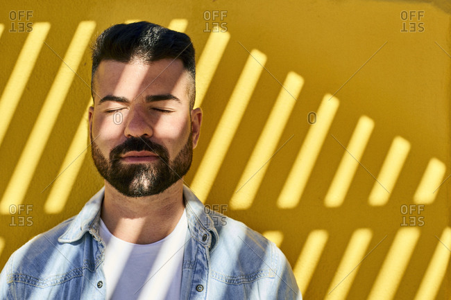 Young man with eyes closed and shadow on face standing against yellow wall outdoors