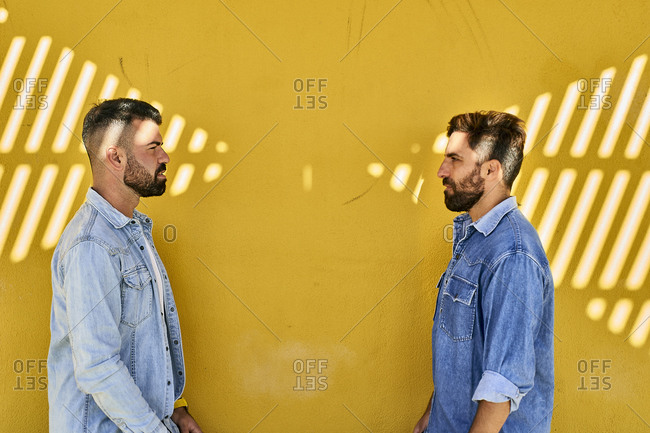 Gay couple looking at each other while standing against yellow wall