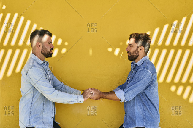 Gay couple holding hands while standing against yellow wall