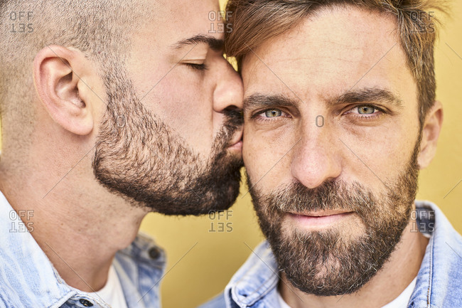 Close-up of gay kissing man while standing against yellow wall