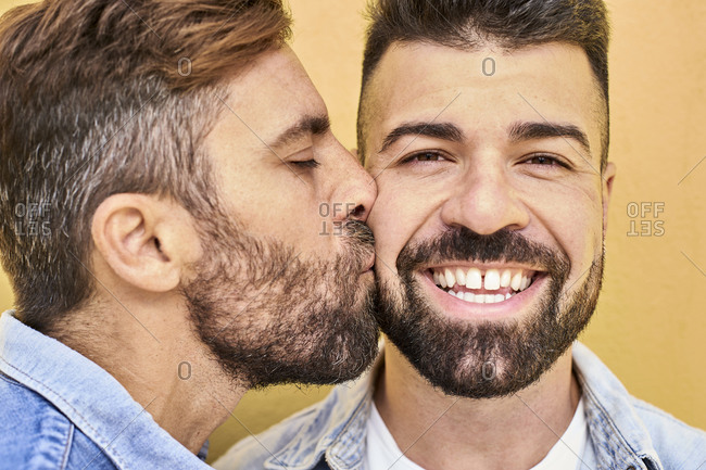 Gay kissing smiling man while standing against yellow wall