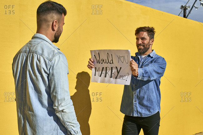 Man holding paper with written text Would You Marry Me on it while standing by yellow wall
