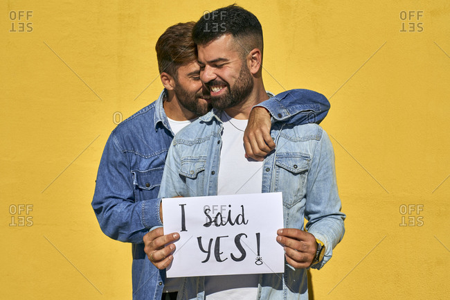 Gay man embracing young man holding paper with text I Said Yes written on it against yellow wall