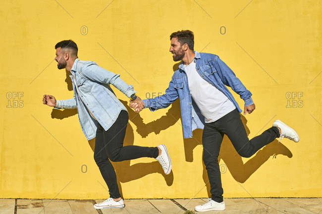 Gay couple holding hands while running against yellow wall