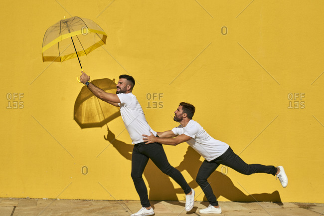 Male couple catching umbrella while standing against yellow wall