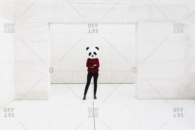 Woman wearing panda mask standing at doorway against white wall