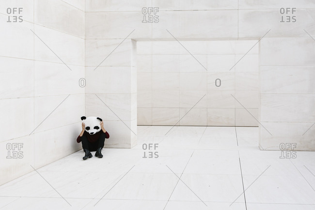 Woman wearing panda mask sitting in corner against white wall