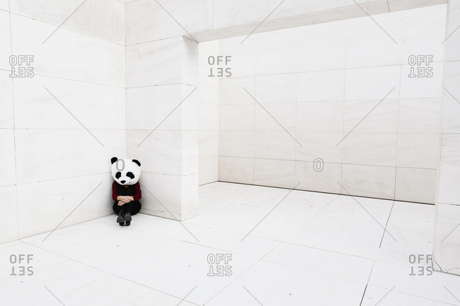 Sad woman wearing panda mask sitting in corner against wall