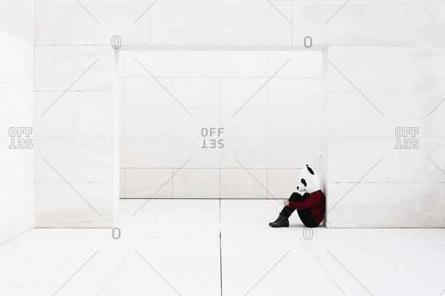 Depressed woman wearing panda mask sitting at doorway against white wall